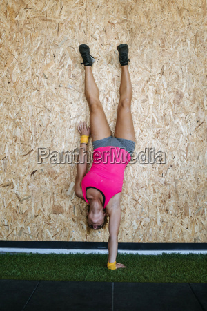 woman doing a handstand with one