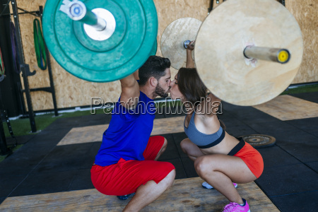couple kissing while lifting barbells in
