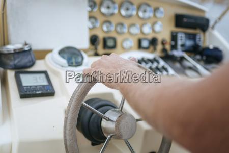man steering motor boat close up