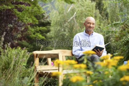 senior man sitting on garden bench