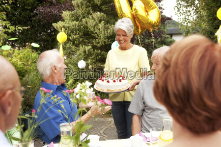 mature woman serving birthday cake