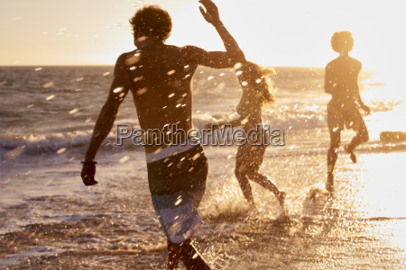 playful friends on the beach at