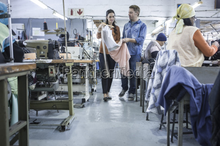 designers in factory discussing dress
