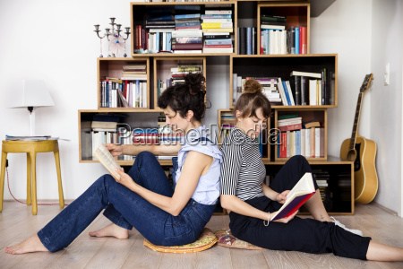 two reading friends sitting back to
