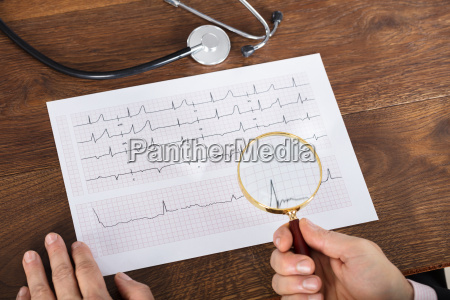 person analyzing cardiogram chart using magnifying