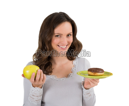 woman holding green apple and donut