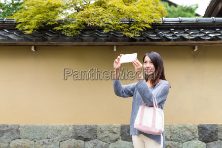 woman taking photo at japanese city