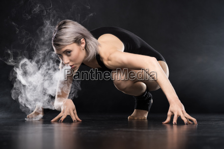 woman in bodysuit exhaling smoke on