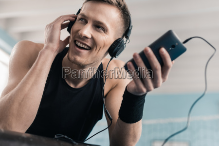 smiling young sportsman in headphones using