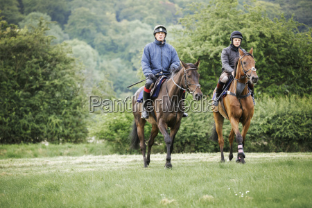 zwei maenner auf bucht pferde ueber