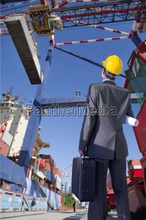 businessman watches loading of containers at