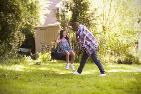 father pushing daughter on tire swing