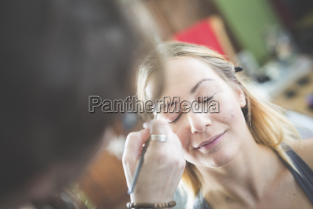 stylist applying make up on womans