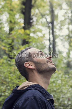 smiling man in the woods looking