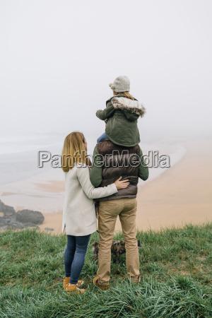 family with dog at the coast