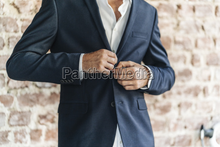 close up of of businessman buttoning