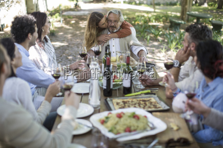 adult daughter embracing father during lunch