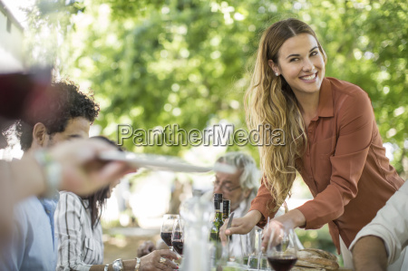smiling woman dishing up at family