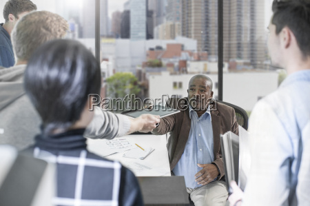 businessman handing over digital tablet in