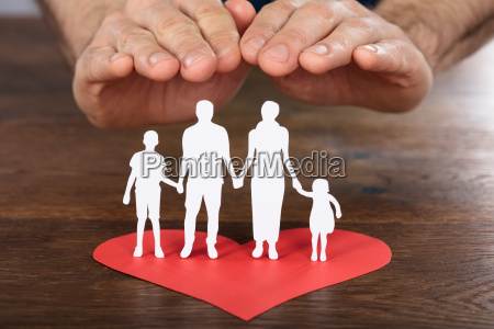 person hand protecting family paper cut