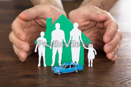 person protecting house model with family