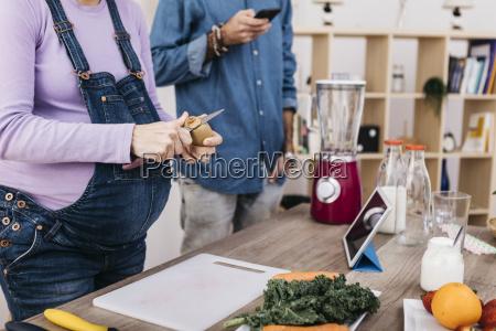 woman peeling kiwi for preparing fruit