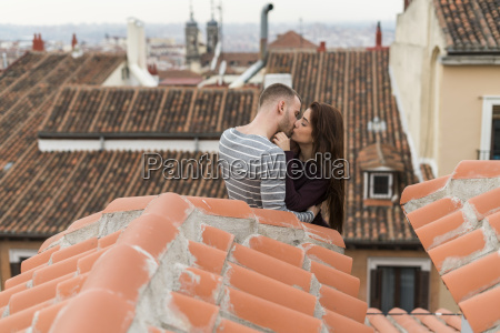amorous couple sitting on rooftop kissing