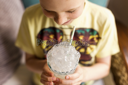 playful boy making milk bubbles with