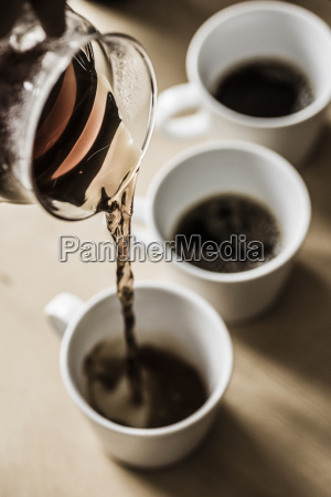 pouring filter coffee into mugs