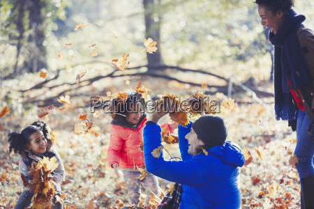 playful father and daughters throwing autumn