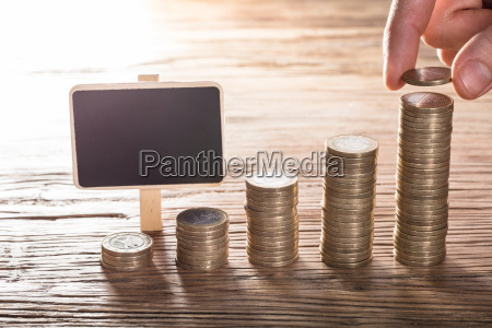 person placing coin over the stack