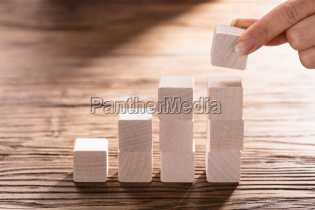 human hand holding a block to
