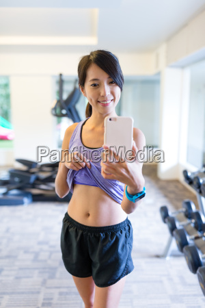 sport woman with smartphone taking mirror