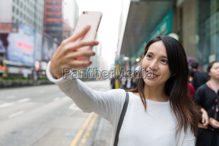 woman taking selfie with cellphone in