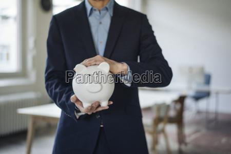 close up of businessman holding piggy