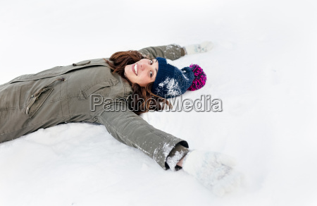smiling young woman lying the snow