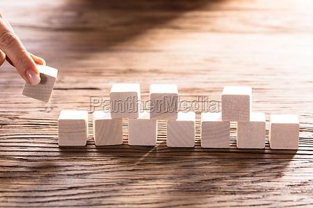 person hand arranging blocks
