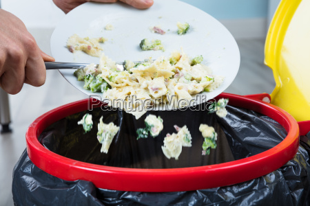 person throwing cooked pasta in trash