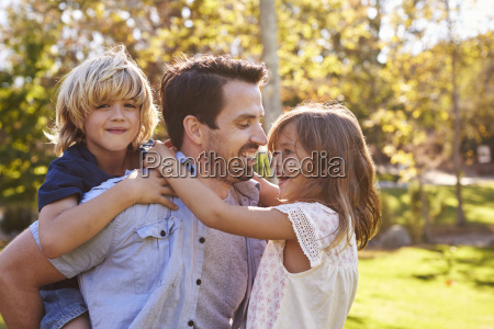 father carrying son and daughter as