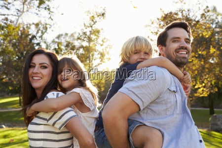 parents carrying son and daughter as