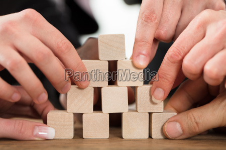 people arranging block on pyramid