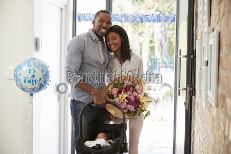 parents arriving home with newborn baby