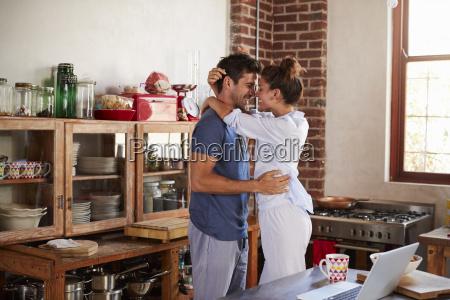 happy hispanic couple embracing in kitchen