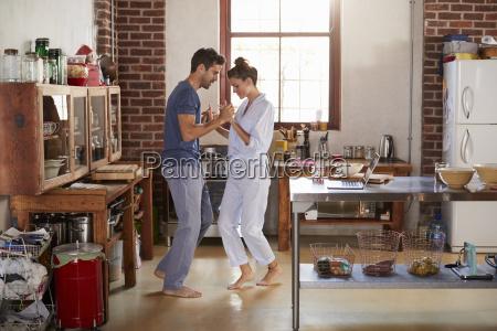 hispanic couple in pyjamas dancing in
