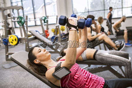 young woman exercising with dumbbells in