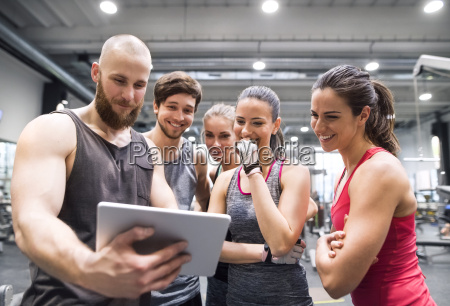 group of happy athletes with tablet