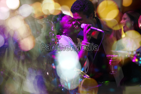 man embracing singer on a party
