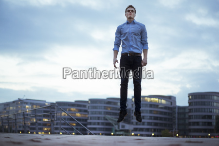 portrait of young man jumping in