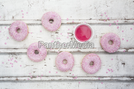 six doughnuts with pink icing and