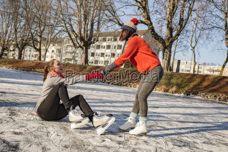 woman helping ice skating friend getting